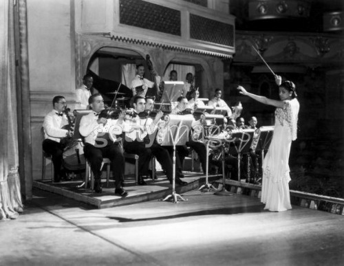 Valaida Snow conducting the orchestra on the set of the show Blackbirds at The Coliseum in London. 1934. Photograph by Sasha.