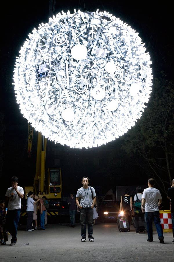 """Artificial Moon"" by artist Wang Yuyang is a sculpture composed of hundreds of energy saving light bulbs of different shapes and sizes. Wang Yuyang, born in 1979, is an accidental new media artist. Interested in obsolete technology, an aesthetics of the broken, and material waste, his practice involves highly conceptual installation, photography, and video. Recent works have carried on the tradition of the post-sense sensibility generation, employing humorous and pseudo-spectacular tactics to interrogate the relationship between body, experience, and cognition. His work has been shown in major exhibitions and festivals across China and Europe"
