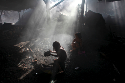 "© Lisa Wiltse. A young girl at work searching for nails in charcoal pits to sell for a few pesos. More of this series can be found here—and thanks Lisa Wiltse for making your images of children in the Ulingan slum in Manila beautiful so that we can really take in the wretchedness they convey. Not just wretchedness comes across, but bravery, of the children themselves, and of Lisa, for stepping right into it with them so we can see too. Lisa's ""Bolivian Mennonites"" exhibit is at The Half King til 7/23."