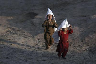 delucazade:  Afghan refugee children with bags on their heads are in the sun in a slum on the outskirts of Islamabad. Pakistan. (AP Photo / Nathalie Bardou)