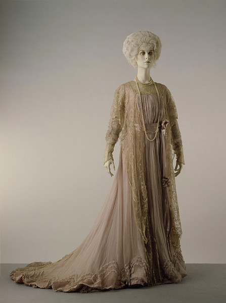 Worth | Tea Gown | c. 1900 The elaborate and luxurious decoration on this gown characterises fashionable 'at home' wear of the late 19th century and early 20th. It was worn by the mother of Lady Hoyer Millar. In September 1900 The Queen, The Lady's Newspaper described the ideal tea-gown: 'It is quite a perfect gown showing soft falling kilted flounces at the hem, silk muslin or silk serving to enhance the beauty of incomparable lace'.