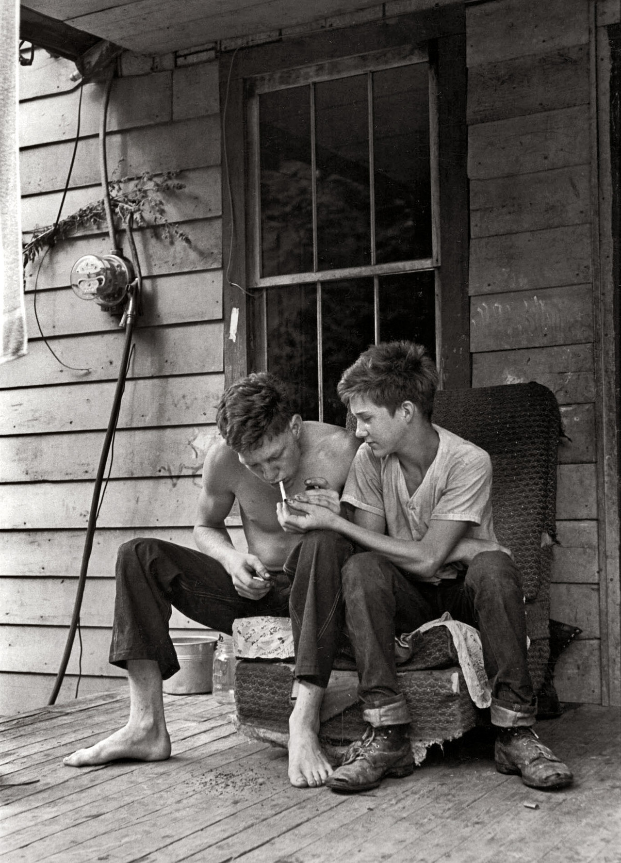 bygoneamericana:  Boys sitting on porch lighting cigarette. Leatherwood, Kentucky, 1964. By William Gedney