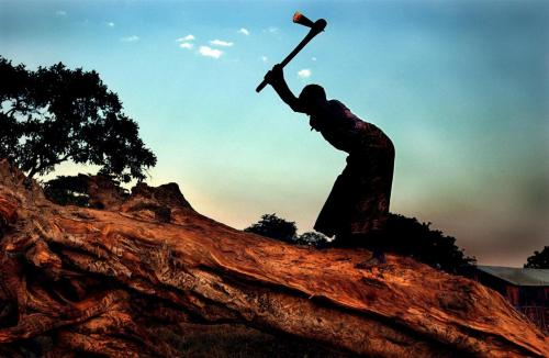 A woman chops wood to sell for food on a hillside already affected by soil erosion, in the village of Chipumi, Malawi. The area is suffering from growing deforestation as people chop down trees for fuel and to make room for agriculture. Because of droughts and flooding, many Malawians were unable to buy seeds to grow their own food crops. © UNICEF/NYHQ2002-0260/Ami Vitale http://www.unicef.org