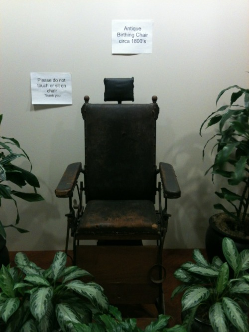 Antique Birthing Chair, making patients feel warm & cozy, at the entrance of a gynecologist office in Houston, TX.
