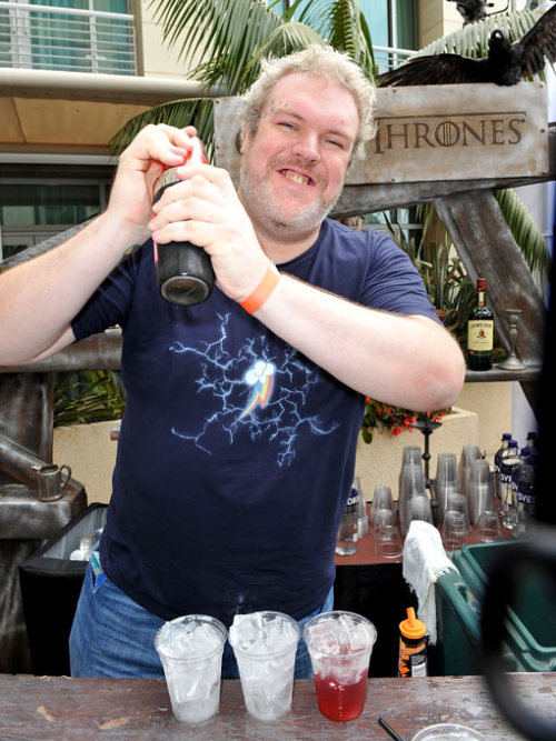 Hodor is making drinks while wearing a Rainbow Dash shirt. wat