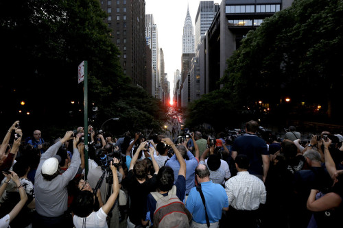 inothernews:  SUN SCREENED   People aimed their cameras as the sun set between buildings on 42nd Street in New York Wednesday. Manhattanhenge, sometimes referred to as the Manhattan Solstice, happens when the setting sun aligns with the east-to-west streets of the main street grid. (Photo: Julio Cortez / AP via The Wall Street Journal)