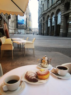 arinacretu:  another thing I like about Italy - the coffee culture. around every corner there is a cafe/bar where one can have a coffee. some of the coffee shops open as earlier as 6 am. and every morning you would have the fresh pastry. the price is more or less the same regardless of the location. 1 euro for a coffee.  and usually Italians drink the coffee at the bar, standing. but we asked if we can have a seat :) p.s.: in this photo it's 6:30 am, a cafe behind Duomo di Milano (Milan Cathedral)