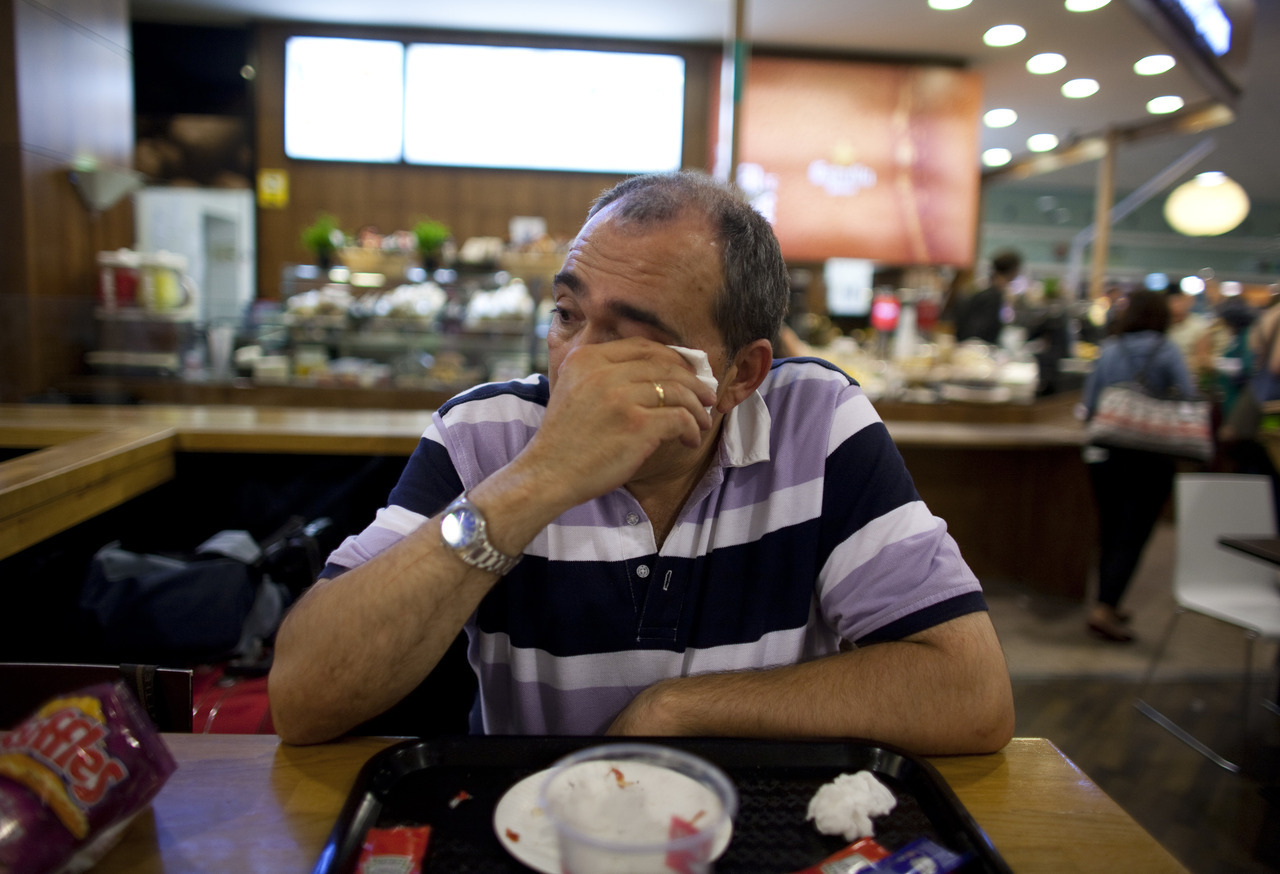 Jose Manuel Abel, 46, cries as he waits to catch a flight to Munich at El Prat airport in Barcelona June 29, 2012.  A former salesman, Abel has been unemployed for more than two years. He has decided to leave his family and move to Germany to work in a Spanish restaurant. His family hopes to join him if his wife can find a job.  Abel arrived in Munich with 250 euros ($307) in his pocket. Picture taken June 29, 2012. REUTERS/Marcelo del Pozo] PHOTO BLOG: A new life with 250 euros