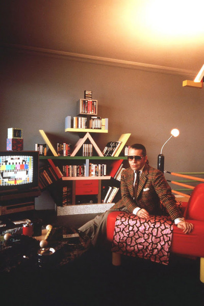asuitablewardrobe:  A younger Karl Lagerfeld conventionally dressed.  …and the Memphis shelves in the background too.