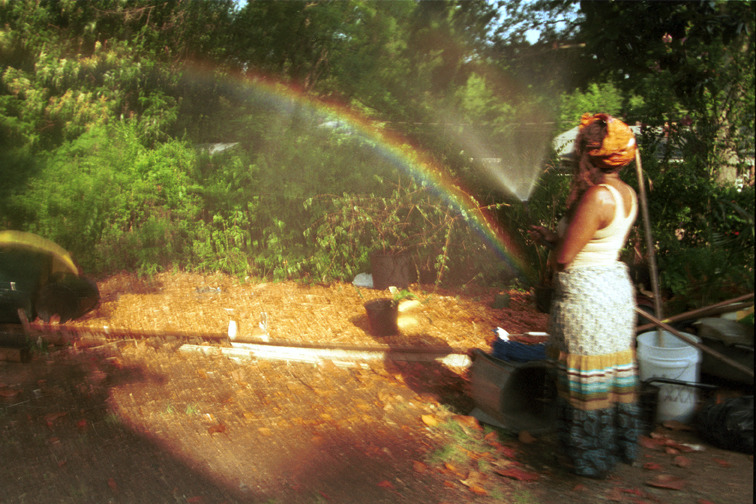 Tina in the garden with a rainbow. Photo by Elijah Kelly. ©Photoworks945