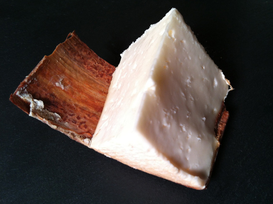 Hölzige Geiss, aka Wooden Goat, from cheese maker Willi Schmid, maker of the previously reviewed Jersey Blue and a somewhat legendary figure in the new wave of small-scale Swiss cheese making (Newlyswissed.com had a good profile of him, and Schmid recently held a talk and tasting at the new Bedford Cheese Shop location in Irving Place which I sadly couldn't attend). Willi's creamery is located in Lichensteig, in the Toggenburg valley of the Thur River, in the Swiss Canton of St. Gallen.  The Hölzige Geiss is a bark-wrapped wheel, similar to a Vacherin Mont d'Or (or Rush Creek Reserve, Jasper Hill's Winnimere, or the many other Vacherin-inspired cheeses now dotting the landscape), in appearance if not in flavor. It is in some respects an unusual cheese; I'm not sure if this is always the case, but the  bone white, lightly eyed paste is much firmer than one would expect from these style of cheeses and has a slightly spongy, even — as fellow urban cheese maker Jon Bonanno described it — marshmallow'y feel to it. this is not a girdled cheese that you would slice the top off of and eat with a spoon, although that being said, you might plow through the wheel just as quickly once you sample it.  In taste as well it's hard to quantify: with a pungent washed-rind, sticky to the touch and aromatic, it is mild up front but with a sweet, tangy, complex flavor, with hints of nuts and grass, and with a distinctly arboreal flavor from the fir bark, especially at the rind, like standing in a pine grove with the smell of the pine tar wafting off the trees. There is a slight bitterness as well, almost like a vegetable rennet cheese but attributed in this case, I suspect, to the bark, as I'm pretty sure this is an animal-rennet cheese. There's very little goatiness at all in this cheese. Like all of Schmid's cheeses, a delicious, if slightly unusual, specimen.  You can see video of Willi Schmid at work in this segment from Swiss television (in Swiss German only unfortunately). At 3:35 you can see him girdling the Hölzige's with bark.