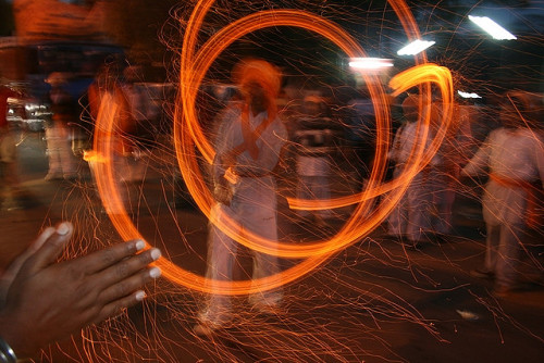lohri by Sun Pictures / Lakshman on Flickr.Via Flickr: Sikh boy spinning fire, on the streets of Kalkaji.  ______________________ Lohri, is celebrated every year on 13th of January. It is a festival to worship fire. Lohri Festival is celebrated with great pomp in North India. At this time Earth starts moving towards the sun marking the auspicious period of Uttarayan. First Lohri is very important for the newly wed and the new born babies as it marks fertility. At night, people gather around the bonfire and throw til, puffed rice & popcorns into the flames of the bonfire. Prayers are offered to the bonfire seeking abundance & prosperity. People make merry by dancing & singing traditional folk songs.