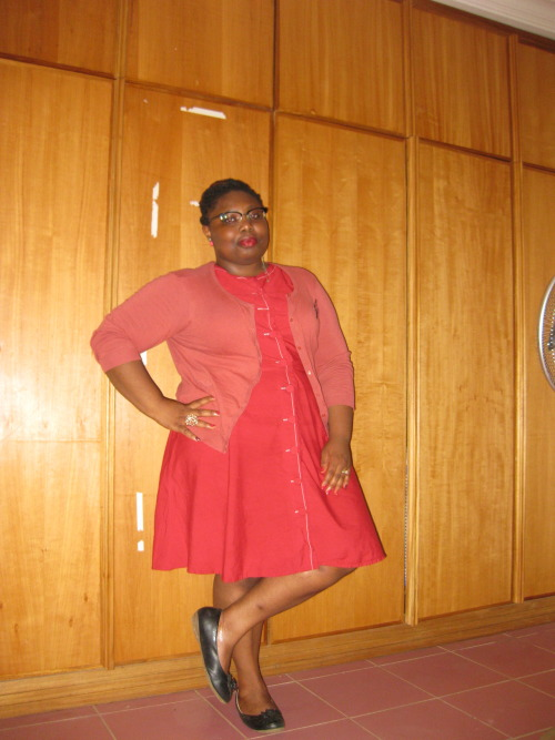 fatpeopleofcolor:  A fat West African woman leaning against her wardrobe doors, with her right hand on her hip and her legs crossed. She is wearing a red dress and a pink cardi. There's a slight smile on her face, she has red lipstick on and her glasses are faux Clubman's. Her jewellery is costume, the earrings are pink apples, the ring on her right hand is a glass flower, while the ring on her left hand is a gold band. Her shoes are black flats.  Earrings and rings- ASOS, New Look and Evans Glasses - Zenni Optical Cardi - H&M Dress- ASOS Flats- SimplyBe