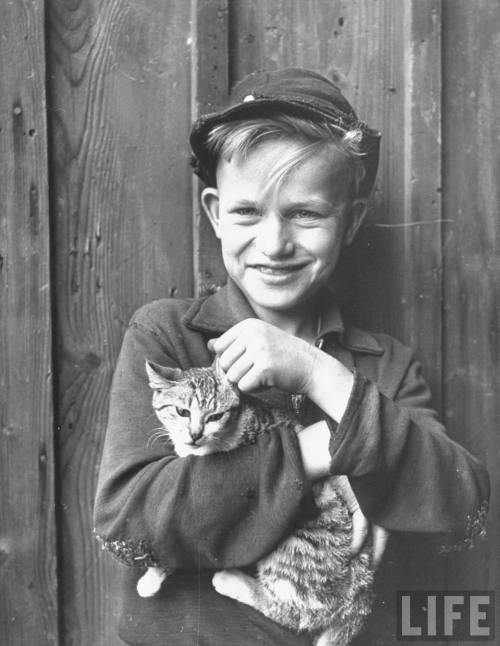 themafucage2:  Close-up of village boy holding cat and smiling Photographer: Walter Sanders Hesslar, Germany, August 1946. © Time Inc.