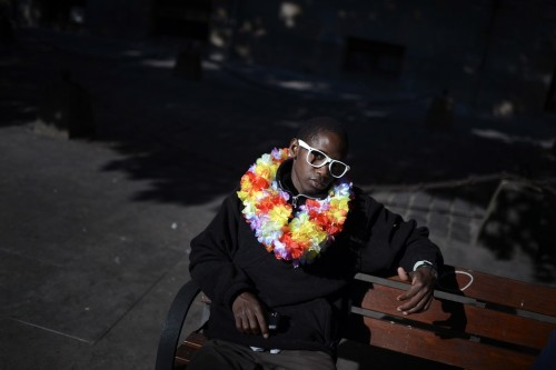 Street vendor Kissima Kebe, originally from Senegal, sat on a bench in the Plaza de Recoleta during Spain's San Fermin festival Monday. Mr. Kebe says he expects to make around €30 on a good day, though sometimes police sometimes confiscate his goods. (Vincent West/Reuters) July 9th, 2012