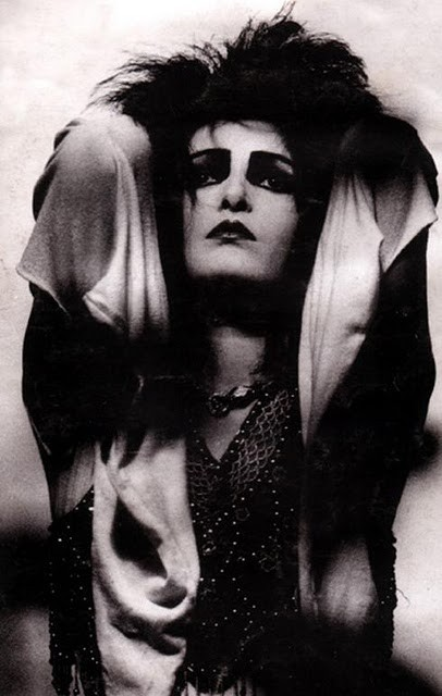 [B/w photo of Siouxsie, glamorous, crisscrossed with light and shadow]