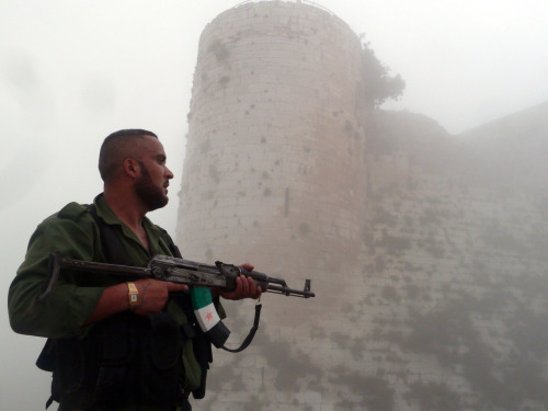"""A member of the Free Syrian Army stands near a medieval castle outside Homs."" [Greg Crowley]"