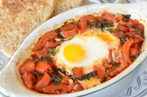 Tomato Poached Eggs This is my favorite summertime breakfast. I posted this recipe a long time ago, but recently told my friend Molly about it because she was looking for something easy and healthy. She tried it and loved it, so I'm sharing it again. The simmering tomato liquid poaches the egg and makes it taste fantastically delicious! This is so easy, takes only about 4 ingredients, and uses up all those garden tomatoes. Heat oven to 375. Chop any fresh tomatoes you have on hand, about 1 cup, and place them in a small casserole dish. Add 1 minced garlic clove. Drizzle with olive oil, season with salt and pepper, and toss it all together.  Bake until bubbly, about 10 minutes.  Remove the dish from the oven and scoot the tomato pieces to the edges. Crack an egg into the center, add fresh chopped basil, (optional). Bake for an additional 5 minutes or so until the egg is done to your liking.  Serve with crusty sourdough toast to soak up all those stewed tomatoes. Yum!