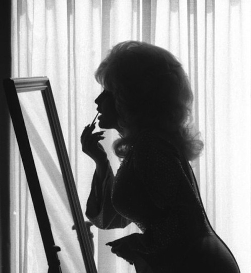 the wonderfully curvy dolly parton re-adjusting her make up.