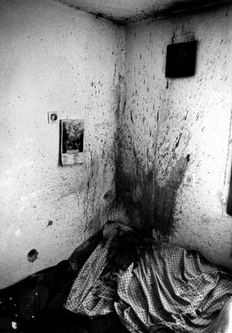 "simply-war:  Bosnia and Herzegovnia - War - Uzdol Massacre ""Blood is spattered high onto the ceiling of a central Bosnian farmhouse. An elderly married couple had been sprayed at point blank range with high velocity machine gun fire in a grisly execution by Bosnian Serb Forces in the Village of Uzdol, Bosnia. Their heads exploded instantly, spraying arterial blood onto the walls. The white fragments at the bottom left of the photograph are the shattered remains of the old couple's skulls. Although I was present when the bodies of the old couple were still lying on the bed, the image was far too horrific for anyone to publish and also, in my mind, quite unnecessary to photograph. However as I turned and was about to leave with the British United Nations soldiers who had the awful task of cleaning up this ungodly horror, one of the young soldiers carrying the remains and I looked back at the wall and I knew I had the shot."" -Sebastian Rich, 1992"