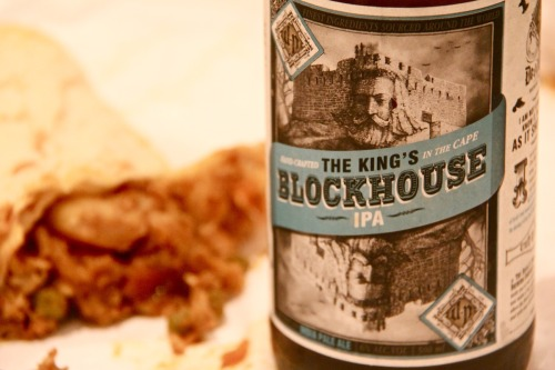 Pro tip: destroy your palate with a Devil's Peak King's Blockhouse IPA (IBU: 56) and a Sunrise vegetable roti (SHU: around 1 million). Rounded bitterness and pricks of citrus and pine from the King's Blockhouse will prime your tongue for what is to come once you unwrap the mummified beast: a burning assault of quasi-pickled cabbage, carrot and green bean, all wrapped up in doughy warm roti goodness. At the end of it, your stomach will feel like it has endured a short but brutal North African coup d'état, and the only movements you're likely to make for the next hour will be moans of pain-laced pleasure.  It's S&M for your intestines, so 50 Shades of Grey that shit up and do it. The beer's more expensive than the roti, but I've been eating these forearm-sized rolls of pure carb-gasm since I was 16, so I'm not going to stop anytime soon. I have, however, found its natural partner. The King's Blockhouse is the only beer I've had that not only stands up to a Sunrise veg roti, but enhances it. Sure, there are bitterer IPAs out there – Triggerfish's excellently pungent Titan IIPA comes to mind immediately – but something about the full spectrum of KB's bittersweet floral-citrus-resin palate brings the pairing to an overwhelmingly indulgent fast food fruition. Sunrise House of Curries, Main Road, Mowbray. Don't eat anything with prawn in it. — If you'd like to get hold of this beer, head on over to League of Beers and have it delivered straight to your door!