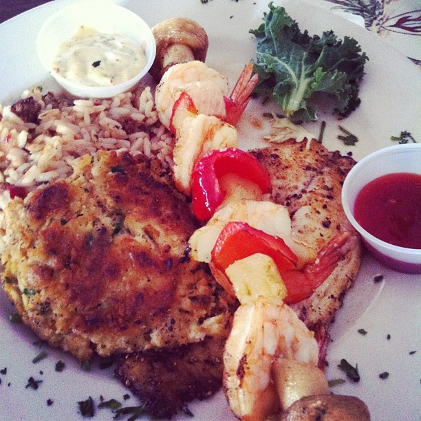 Tilapia, crab cakes, shrimp kebobs and dirty rice! (Taken with Instagram)