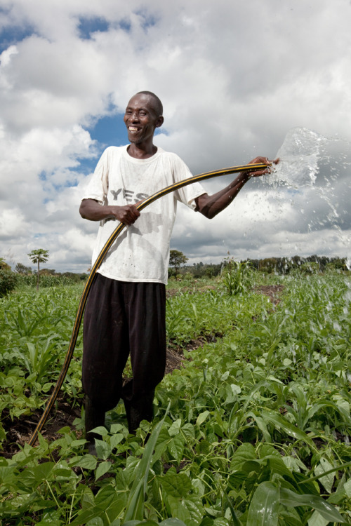 Johnson, a rural farmer in Kenya, smiles as he uses his Kickstart irrigation pump on his 3.5 acre farm. Learn more at theadventureproject.org.