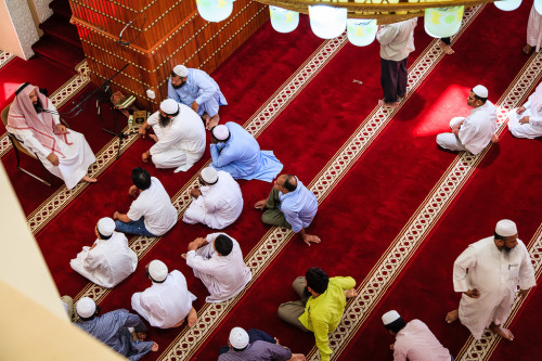 Muslim men gather around the imam for a talk after Friday prayers in a mosque on Musheireb Street.