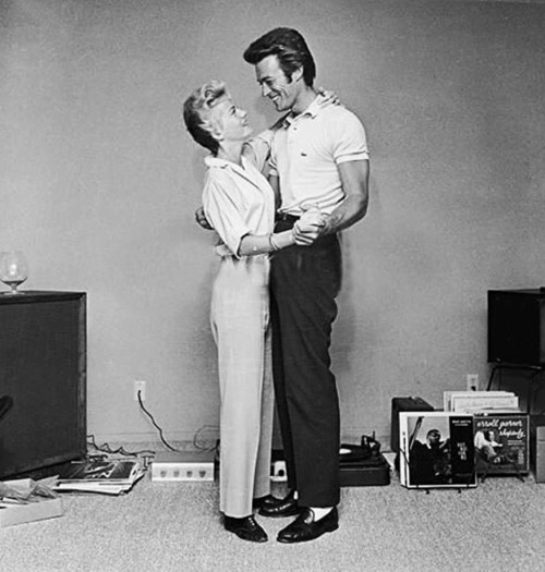 Clint Eastwood and his first wife, Maggie, dance next to a turntable and a rack full of records in a living room in 1965.