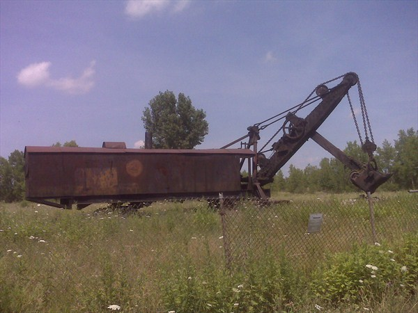 "steampunkvehicles:   The Le Roy MarionThe world's largest steam shovel surviving intact is a 1906-built Marion machine, located in the small American town of Le Roy, New York. This machine was bought by the General Crushed Stone Company, who operated the largest rock crusher in the world at a quarry in Le Roy. The shovel, which weighed over 100 tons, was originally mounted on flanged rail-wheels, but was converted to caterpillar tracks in 1923 using a conversion kit manufactured by Marion. A crew of three men were required to operate it: a fireman, who kept the boiler fed with coal and water; a crane man, who sat on the left-hand side of the boom and tripped the 1 5/8 yard bucket by tugging on a wire rope attached to the bucket; and an engineer (or driver), who raised and lowered the bucket and drove the machine along the track. This shovel remained in use until 1949, when it was driven out of the quarry and parked by the main road – where it remains to this day, although no longer functional. The Town Council have purchased the land on which it sits, and are planning to apply (in March 2007) for National Landmark status for the shovel.  Note: The shovel and land are now a historic landmark.So it should be preserved now for posterity.They were considering moving it to alexander NY to the site of the Alexander Gas and Steam show. Maybe a 20 mile trip, but nowadays an impossible route due to height, size, and weight.More info:Made Marionby Lynne BelluscioWe almost missed the 100th anniversary of ""Marion"" the steam shovel on the Gulf Road. The 1906 Le Roy Gazette reported that the 100-ton steam shovel was manufactured in Marion, Ohio for the General Crushed Stone Company, which in 1906 operated the largest rock crusher in the world. The company needed a shovel to load stone from the quarry into the small railroad cars that conveyed the large stones to the crusher. The steam shovel was known as a 5-yard dipper. Originally, when the Marion came to Le Roy, it moved on railroad tracks, which had to be laid in the bottom of the quarry. A crew of men relaid the tracks when the shovel moved to a new rock face.In 1921 the Marion Company manufactured a ""kit"" to change the railroad wheels to caterpillar tracks but it wasn't until 1923 or '24 that the Le Roy shovel was adapted to caterpillar tracks. The Marion shovel worked in the quarry for forty three years and in June 1949 it was driven out of the quarry by Manny Stefani and parked near the edge of Gulf Road where it is now. One of the locomotives and a tip car were displayed with it. (Several years ago, General Crushed Stone gave the ""Dinky"" to a collector near Syracuse and it was moved, much to the dismay of all the people who had worked in the quarry!)The Le Roy shovel is called a partial swing shovel since it doesn't move 360 degrees. The main frame is mounted on two all-steel heavy-duty trucks (sometimes called bogies). The axels are driven by chains and gears from the main, reversible engines on the deck of the shovel. The power for the equipment is a locomotive-type boiler with reversible hoisting, swinging and thrusting (or crowd) engines.The Le Roy shovel has the original Marion boiler, although it is not in operating condition. The lower flues are badly rusted and the doors are broken. Attached to the front of the frame, or car, is the swing circle, on which is mounted the excavating equipment which consists of the boom, the dipper handle, the dipper and the thrusting engines. Unfortunately the thrusting engines are mounted on the boom and have been exposed to the weather and are full of water. The other two engines seem to be in working condition. The boom is split which allows the swing of the dipper handle. The dipper is made of heavy steel plates and the teeth are made of manganese steel. Kermit Arrington told me that his father often removed and sharpened the teeth.The steam shovel was invented by an American, William S. Otis in 1836. It was the first efficient dry-land single bucket excavator and was a partial swing machine, like the Marion in Le Roy. The full swing, revolving shovel was introduced in 1884 in England. The advantages of the revolving shovel was eventually recognized and the railroad shovel was doomed.Although it has been rumored that the Le Roy Marion had been used to dig the Panama Canal, that is not the case.  source:  HAMB"