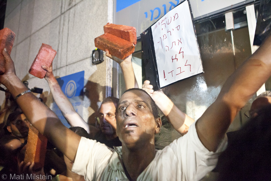 """When I feel the heat, I see the light.""  Protesters in front of the Israeli National Insurance Institute's Tel Aviv offices the day after Israeli man Moshe Silman set himself on fire to protest his crippling economic situation. The sign reads: ""Moshe Silman - You are not alone!"""