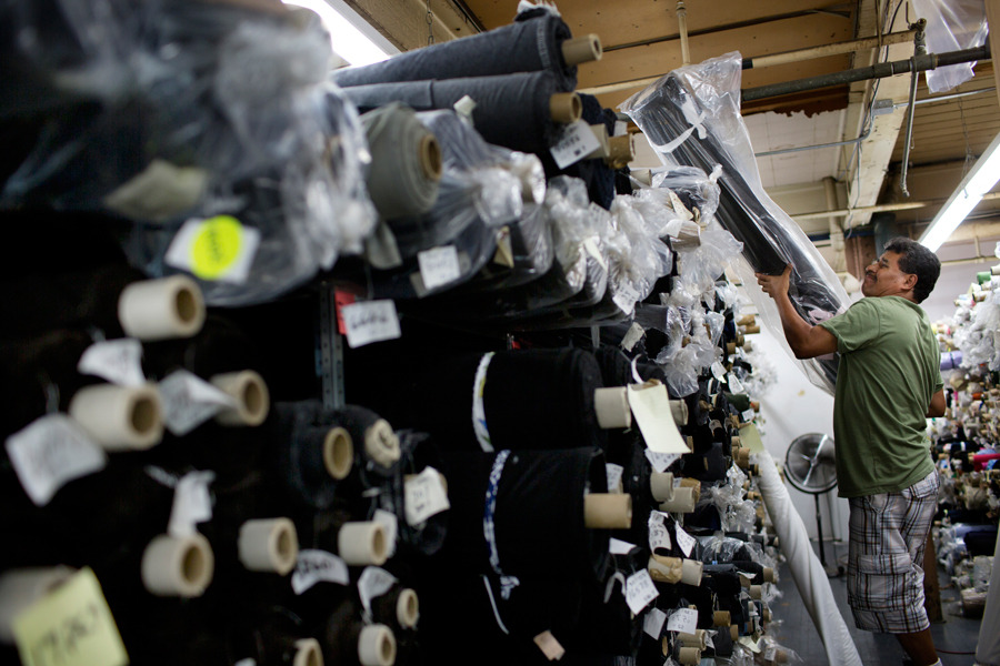 A worker holds a bolt of fabric at Dynotex Inc. garment factory in the Brooklyn borough of New York, on July 11. Photograph by Victor J. Blue/ Bloomberg