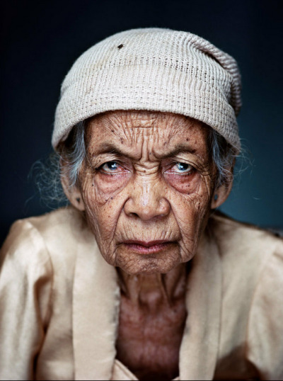 "© Jan Banning, from his series ""Comfort Women,"" a project he made with writer Hilde Janssen. Jan exhibited at The Half King in 2010 with his many-storied, breathtaking project ""Bureaucratics."" Despite their severity, Jan's comfort women portraits are so in keeping with his Bureaucratics portraits: they both occur straight on, with no equivocating, no apology. Here, this woman seems the face both of an unapologetic truth sayer, but also of the specific horror she was subjected to. And the housefly on her knitted cap gives a weird bit of levity to her intense anger and hurt. Comfort women were Indonesian, Korean, or Chinese girls taken from their homes and forced into prostitution by the Japanese military during WWII. Jan's photos are of 18 such Indonesian women. In speaking with Jan and Hilde, these women broke the persistent taboo against publicizing rape, and are part of a growing awareness of this secret history.  Two items of interest related to Jan's project:  1) This past spring, NYC's Queens Council member Peter Koo announced plans for a memorial in Queens that would honor comfort women. Japanese deniers are writing to protest. (Deniers assert that these women were willing prostitutes.)  There is already one such memorial in Palisades Park, NJ. In May, a group of Japanese elected officials met with Palisades borough leaders to ask them to remove the memorial. The answer was no. Read more here.  2) In Tokyo, a photographer Ahn Sehong is exhibiting his ""Comfort Women"" photography—now, as I write—to bitter outrage. In response, Nikon, the show's host, at first cancelled the exhibit, then re-instated it after a court order. They did however, succeed in prohibiting the media from covering the show. More here."