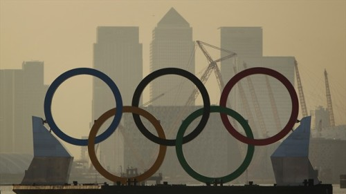 Giant Olympic Rings launched on the River Thames. Measuring 11 metres high by 25 metres wide, a set of giant Olympic Rings travel on a barge past London's Canary Wharf.