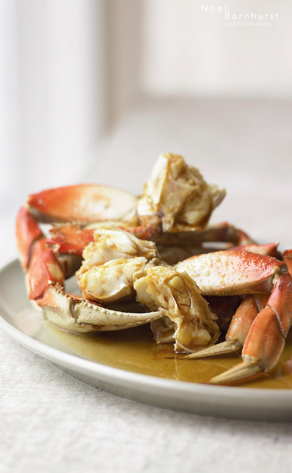© Noel Barnhurst Tangy Ginger Crab Ingredients 1 live Dungeness crab (about 2 pounds) About 1/2 cup Tangy Ginger Sauce, chilled Directions In a large steamer, bring several cups of water to a boil. Place the crab in the steamer, cover, and steam until the crab has turned bright red and is cooked through, about 15 minutes. Remove the crab and let rest until cool enough to handle. Insert your thumb or a knife point between the upper shell and the body, opposite the mouth. Pry off the shell, and then trim off the mouth and other inedible parts. Scrape the yellow-green liver (tomalley) out of the center of the body. Leaving the legs attached, cut the crab in half, down the middle, with a large knife. Then, cut each half into thirds so each piece has legs and body. Crack each section of leg by giving it a good whack with the knife. Be careful not to cut all the way through. Serve the crab on a platter with a small bowl of very cold Tangy Ginger Sauce. Serves 2 to 3.  Tangy Ginger Sauce Ingredients 1/2 cup apple cider vinegar 7 tablespoons sugar 1 teaspoon soy sauce 1/4 cup very finely minced peeled fresh ginger Directions Heat the vinegar, sugar, and soy sauce together in a small pan just until the sugar has melted. Pour the mixture into a bowl, add the ginger, stir well, and refrigerate until cold. The sauce will keep, tightly covered, for several days in the refrigerator. Makes about 1 cup. Recipe courtesy of Modern Asian Flavors by Richard Wong