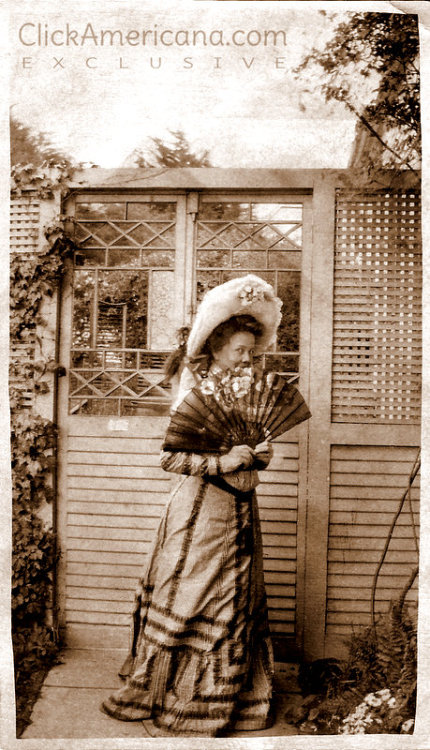 From my family photo collection: A woman in a garden around the turn of the century, coyly hiding behind a fan