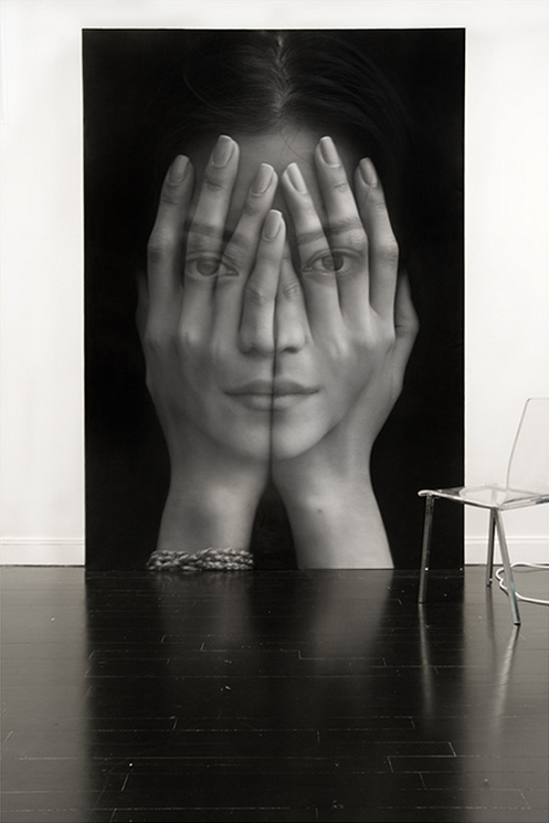 skeletales:  Artist Tigran Tsitoghdzyan was first exposed to oil paints at the tender age of five and quickly adopted the art of painting, perfecting his skills in his youth. The time and effort the Armenia-born painter, who currently lives and works in New York, has put into honing his craft has certainly paid off, allowing him to not only paint hyperrealistic renditions of people, but to peer into their souls with a few masterful layering techniques. Tsitoghdzyan's painting titled Mirror is especially effective at exhibiting this type of artistic translucency. In Mirror, we're able to see every defining attribute of a woman's visage through a pair of hands that are placed over the subject's face, attempting to cloak her physical identity. However, there is no way for this young woman to conceal herself. It is reflective of internet culture in the world we live in, today, where it continually becomes exceedingly difficult to reach any level of anonymity.
