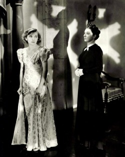 "oldhollywood:  Joan Fontaine and Judith Anderson in publicity still for Rebecca (1940, dir. Alfred Hitchcock) (via) ""Her voice dropped to a whisper. 'Sometimes, when I walk along the corridor here, I fancy I hear her just behind me. That quick, light footstep. I could not mistake it anywhere. It's almost as though I catch the sound of her dress sweeping the stairs as she comes down to dinner.'  She paused. She went on looking at me, watching my eyes. 'Do you think she can see us, talking to one another now?' she said slowly. 'Do you think the dead come back and watch the living?'""  -Daphne du Maurier, Rebecca (1938)"