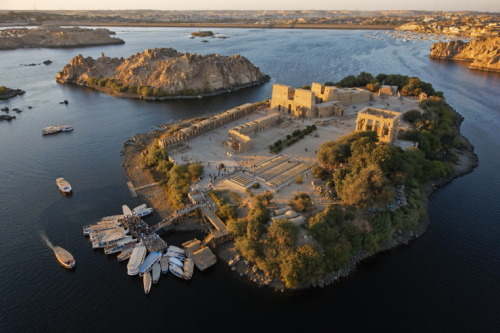 vacilandoelmundo:  Philae, Egypt  Wikipedia:  The island temple was built during the Ptolemaic Dynasty. The principal deity of the temple complex was Isis, but other temples and shrines were dedicated to other deities such as Hathor and Harendotes. The temple was closed down officially in the 6th century AD by the Byzantine emperor, Justinian ( 527-565 AD ). Philae was a seat of the Christian religion as well as of the ancient Egyptian faith. Ruins of a Christian church were discovered, and more than one adytum bore traces of having been made to serve at different eras the purposes of a chapel of Osiris and of Christ.