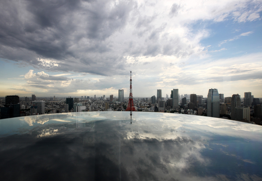 The Tokyo Tower, center, stands amidst the city skyline as the sky is reflected off a glass surface in Tokyo, on July 17. Photograph by Tomohiro Ohsumi/Bloomberg