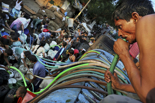 New Delhi — An Indian man sucks on a hose to pull water as a crowd gathers around a government tanker delivering drinking water because of short supply in running water taps. Many areas of the Indian capital are facing acute water shortage, a repeated annual phenomenon during summer when taps go dry as demand rises.
