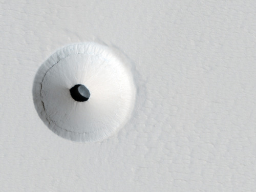 A Hole in Mars What created this unusual hole in Mars? The hole was discovered by chance on images of the dusty slopes of Mars' Pavonis Mons volcano taken by the HiRISE instrument aboard the robotic Mars Reconnaissance Orbiter currently circling Mars. The hole appears to be an opening to an underground cavern, partly illuminated on the image right. Analysis of this and follow-up images revealed the opening to be about 35 meters across, while the interior shadow angle indicates that the underlying cavern is roughly 20 meters deep. Why there is a circular crater surrounding this hole remains a topic of speculation, as is the full extent of the underlying cavern. Holes such as this are of particular interest because their interior caves are relatively protected from the harsh surface of Mars, making them relatively good candidates to contain Martian life. These pits are therefore prime targets for possible future spacecraft, robots, and even human interplanetary explorers.