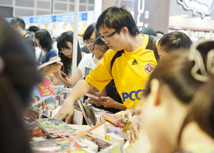 HONG KONG: July 18, 2012 — A man goes through the sales section of the Page One Booth at Hong Kong Book Fair 2012 on July 18, 2012. (Photo by Justin Chin)