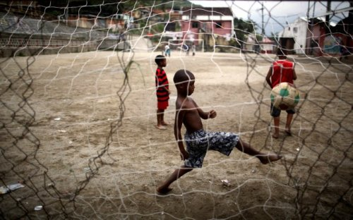 "Where in the World Wednesday. Kids playing ""pelada"" (pick up soccer) in a favela in Brazil. Help support Little Feet mission here and around the world by purchasing a ball for yourself and we'll donate one in kind. www.LittleFeet.com"