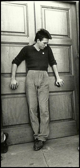 [B/w photo of young Robert Smith standing in a vulnerable, open pose against a door, eyes downcast]