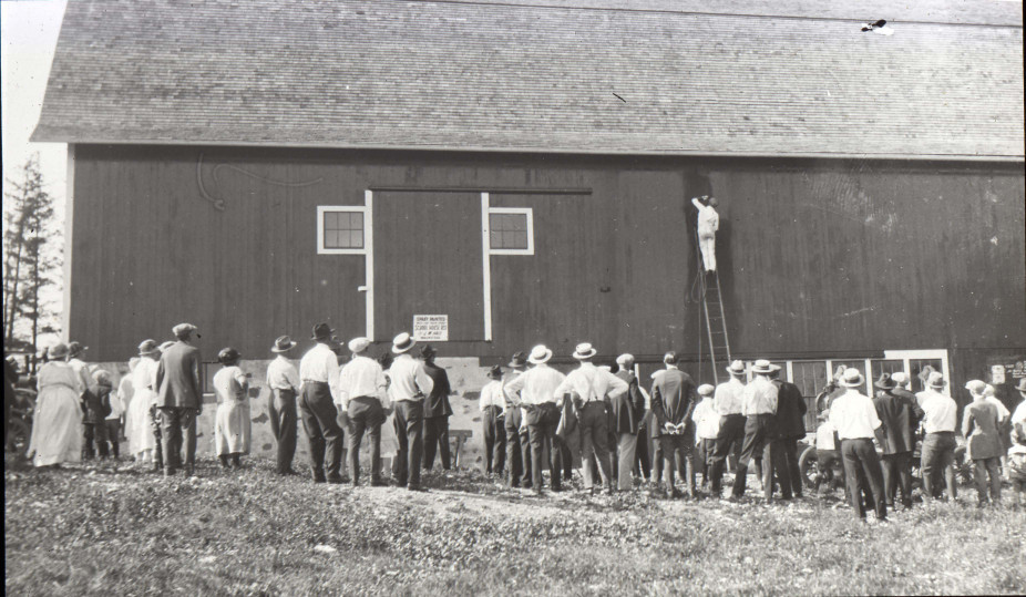 "Crowd watches a man spray paint a barn, Waukesha County, early 20th century. After a barn is constructed, it needs to be painted—apparently an exciting event for this crowd in rural New Berlin, Wisconsin. According to the sign, the paint color is the classic choice for barns—""school house red.""  via: New Berlin Historical Society"