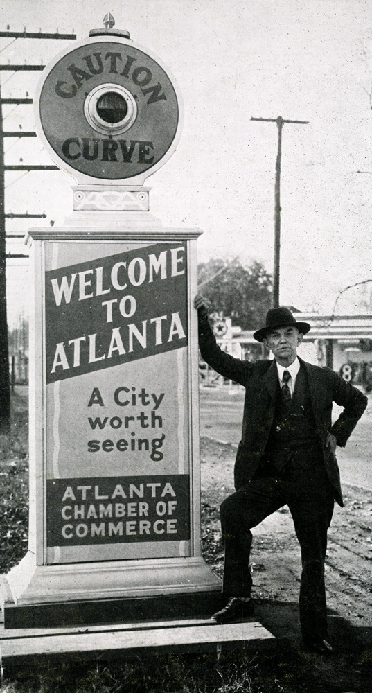 "Atlanta Chamber of Commerce chairman Frank T. Reynolds poses with a ""Welcome to Atlanta"" sign erected in 1930.  Browse and order prints from our collection."