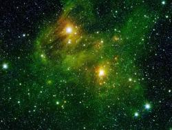 "The basis for all life. Two extremely bright stars illuminate a greenish mist in this and other images from the new GLIMPSE360 survey. This fog is comprised of hydrogen and carbon compounds called polycyclic aromatic hydrocarbons (PAHs), which are found right here on Earth in sooty vehicle exhaust and on charred grills. In space, PAHs form in the dark clouds that give rise to stars. These molecules provide astronomers a way to visualize the peripheries of gas clouds and study their structures in great detail. PAHs are not actually ""green;"" a representative color coding in these images lets scientists observe PAHs glow in the infrared light that Spitzer sees, and which is invisible to us."