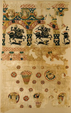 felixinclusis:  fallenangel4: Fragment from a Coptic Hanging. 5th century  Egypt. This large rectangular textile incorporates both Roman and Christian imagery. Arcades containing hunters on horseback recall Roman sources, while the roundels with angels are clearly Christian. Similar imagery, such as the baskets of fruit, is found on the wall paintings of Umayyad desert palaces in Syria. Early textiles such as this, woven by Coptic Christians, have survived the centuries due to the dry climate and the Christian perpetuation of the Egyptian practice of burying the dead in garments sometimes shrouded in large cloth wrappings. Such textiles were woven in well-organized workshops that continued to function in the early Islamic period.