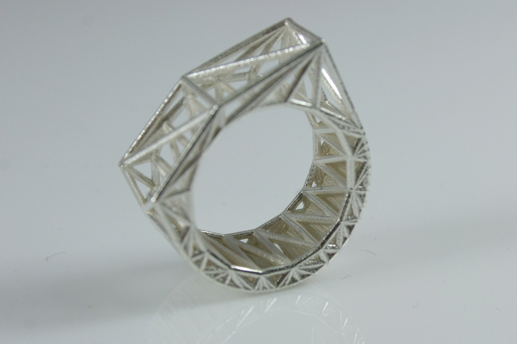 The Structural Chipped Block Ring by Bits to AtomsCelebrating the Digital Aesthetic with honesty of materials and processes the Structural Series reduces the material of the ring to the minimum possible lines needed to describe the form with computer generated triangulation. The texture has a powder like quality that is unique to the Selective Laser Sintering Process which adds to the honesty of the digital process.3D Printed on demand by Shapeways.Please contact me for more information regarding size